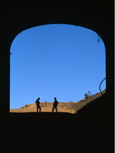 Silhouette of 2 miners outside a mine shaft